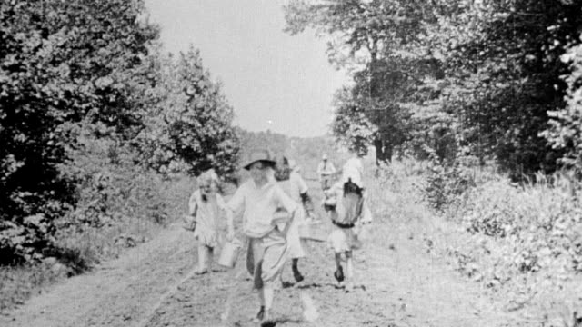 children carrying books and lunch pails as they walk along dirt road to school - 1916年点の映像素材/bロール