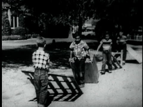 montage b/w ws ts children carrying wood down suburban street / usa - 引きずる点の映像素材/bロール