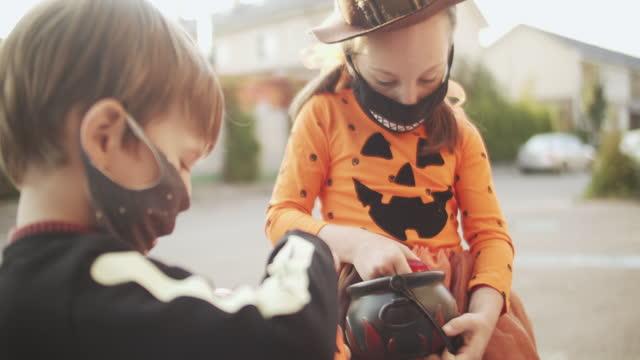 covid-19パンデミック中に保護フェイスマスクでハロウィーンを祝う子供たち - 菓子類点の映像素材/bロール