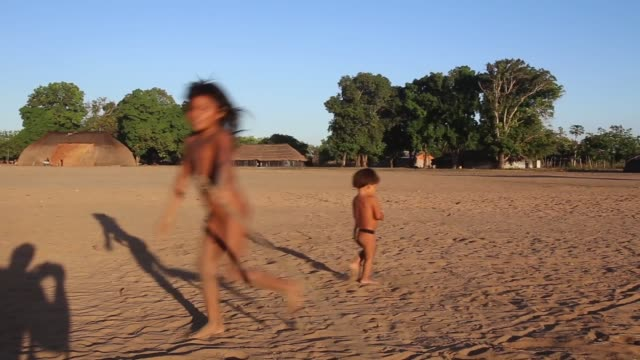 vidéos et rushes de pan children chase and play in kamayura village shot on june 14th 2014 - culture indigène