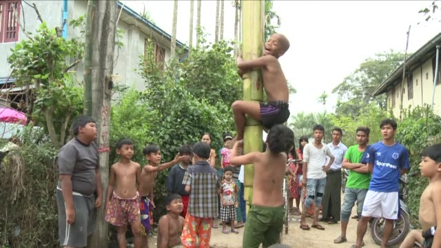 children clamber up oiled banana stalks as teenagers wrestle for greasy coconuts in street fairs hold around yangon to celebrate myanmar's 70 years... - slip banana stock videos & royalty-free footage