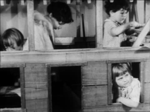 b/w 1934 children cleaning playing in playhouse in nursery school / wpa project / newsreel - anno 1934 video stock e b–roll