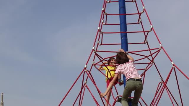vídeos de stock e filmes b-roll de children climbing on play equipment - corda