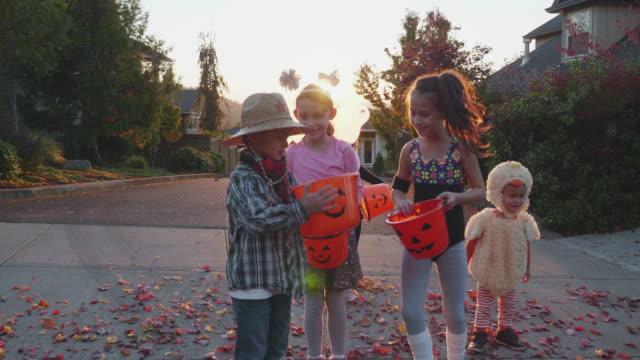 kinder vergleichen eimer mit süßigkeiten für halloween - halloween stock-videos und b-roll-filmmaterial