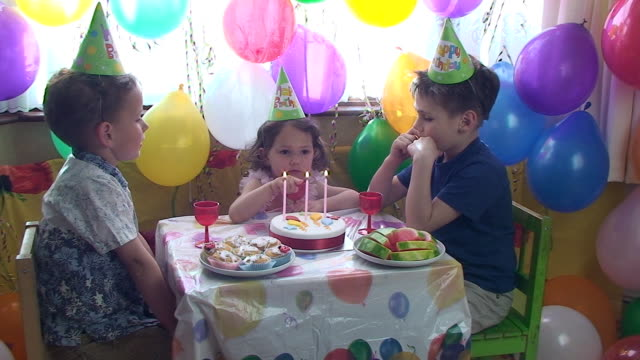 Children counting candles on the birthday cake