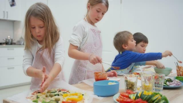 クッキングワークショップで自分のピザを作る子供たち - 切る点の映像素材/bロール