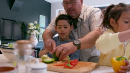 Children cutting vegetables - preparing food together with their father