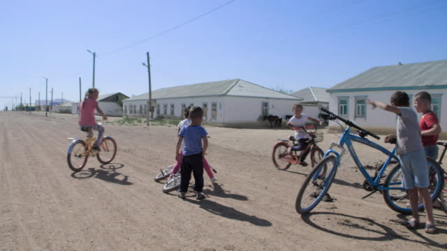 children cycle in an ex-fishing village formerly next to the aral sea, kazakhstan. - 水産業点の映像素材/bロール