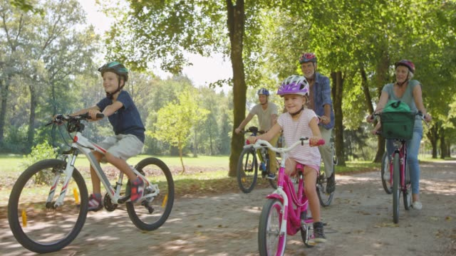 ts children cycling in the sunny park with their parents and grandparents - sports helmet stock videos & royalty-free footage