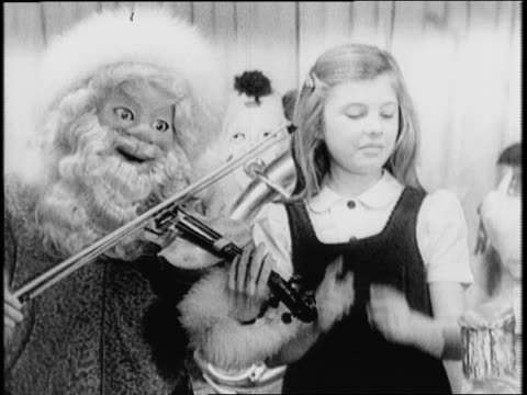 Children dancing with toy orchestra / animatronic band of clowns and Santa Claus playing instruments / Santa plays violin little girl dances / clowns...