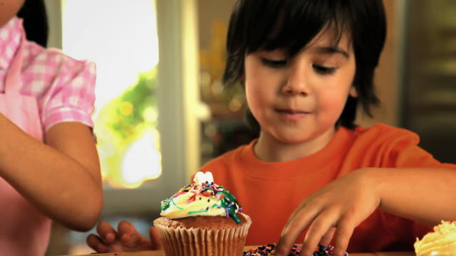 vídeos de stock, filmes e b-roll de ms children decorating cupcakes with sprinkles / los angeles, california, usa - sprinkles