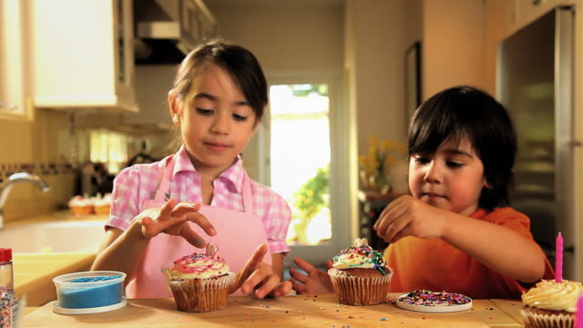 MS Children decorating cupcakes with sugary bits / Los Angeles, California, USA