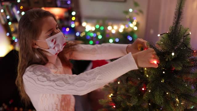 vídeos de stock e filmes b-roll de children decorating the christmas tree during the covid-19 pandemic - enfeitar a árvore de natal