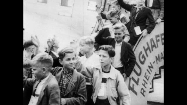 vidéos et rushes de / children descend steps of plane waving and smiling / children walk into a camp that has sign 'jugendlager klein berlin herzuch wilkommen' [welcome... - 1953