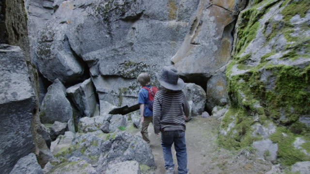 vidéos et rushes de children descend through rock canyon - découverte