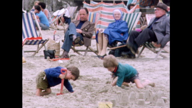 children dig holes in sand and make sandcastles; 1975 - outdoor chair stock videos & royalty-free footage