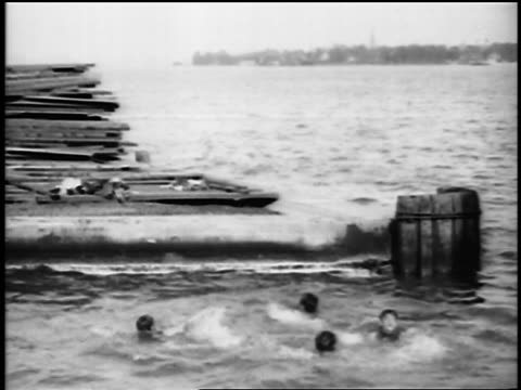 b/w 1915 children diving off of platform into lake/river + swimming / newsreel - swimming costume stock videos & royalty-free footage
