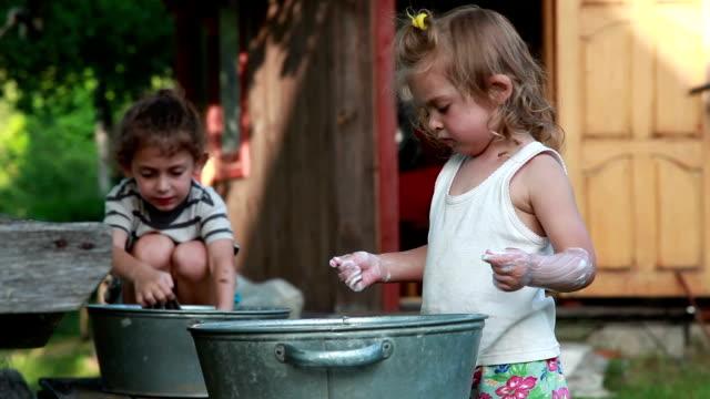 vidéos et rushes de enfants faisant la lessive dans l'arrière-cour - lessive corvée domestique