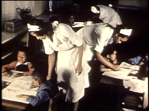1940 montage children drawing pictures as young women supervise / united states - school uniform stock videos & royalty-free footage