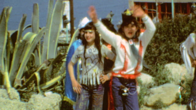 children dressed in costume are escorted by their teachers / looking out over ocean / purim costumes on march 08 1974 in acre israel - iran stock-videos und b-roll-filmmaterial