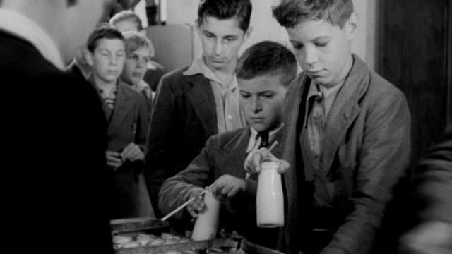 1940 montage children drinking milk at school / united kingdom - 1940 stock videos & royalty-free footage