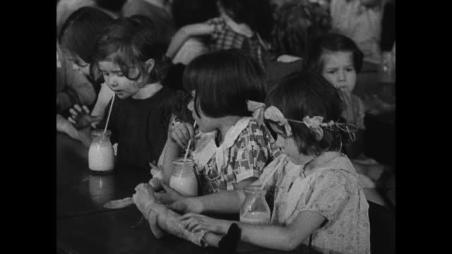 stockvideo's en b-roll-footage met children drinking milk in school room boy drawing funny face on blackboard vs children drinking milk from small glass bottles - drinking health 1930 film