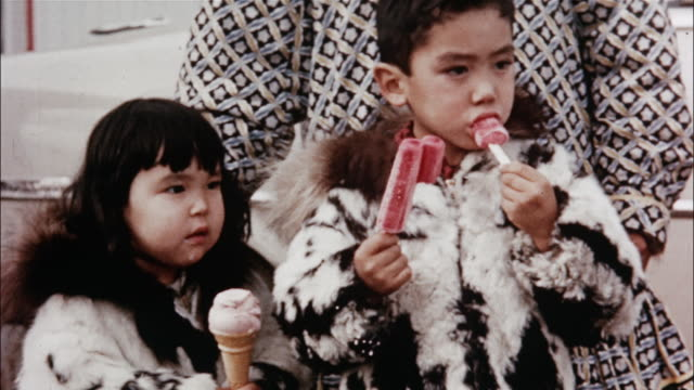 Children eat ice cream and popsicles while two men talk.