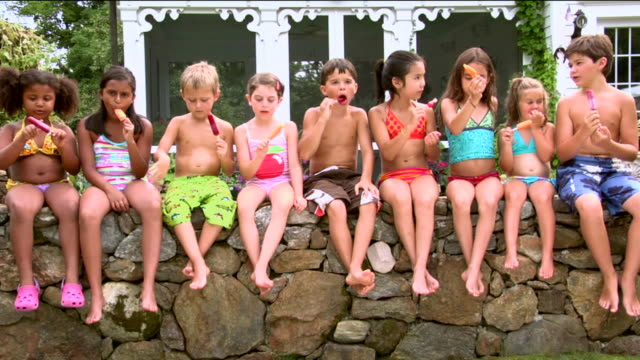 ws zi ms pan children eating frozen popsicles side by side on stone ledge / sherman, ct, usa - side by side stock videos & royalty-free footage