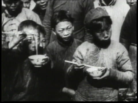 1932 WS Children eating noodles out of bowls with chip sticks / China