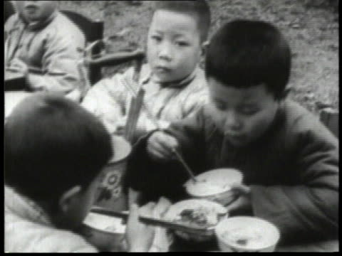 1932 MONTAGE Children eating noodles with chop sticks, feeding a baby, and drinking soup out of a bowl / China
