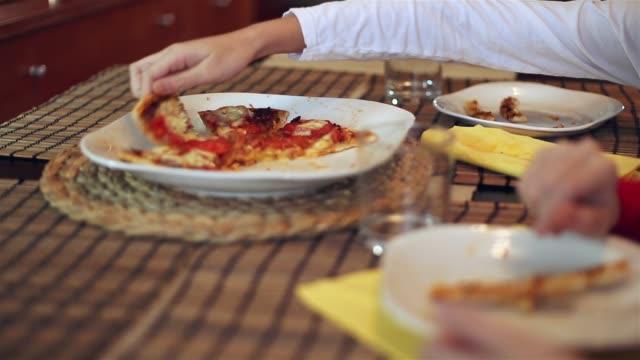 children eating pizza. - greifen stock-videos und b-roll-filmmaterial