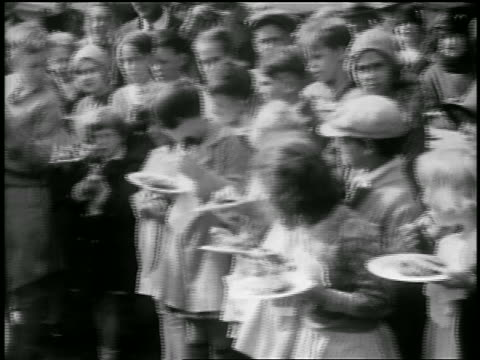 b/w 1929 pan children eating slices of world's largest pie outdoors / albion, ny / newsreel - 1920 1929 stock-videos und b-roll-filmmaterial