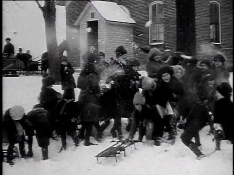 1916 ws children engage in snowball fight as adults supervise / united states - wide shot video stock e b–roll