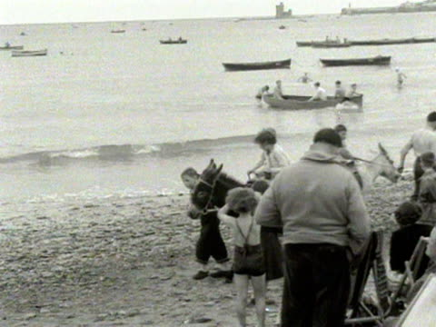 children enjoy donkey rides on the beach at douglas isle of man 1954 - ice cream cone stock videos & royalty-free footage