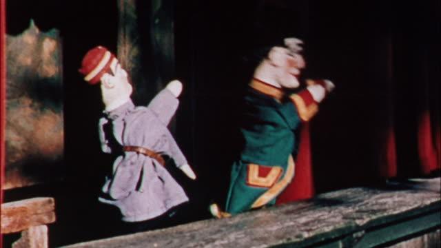 vídeos de stock e filmes b-roll de children enjoy rides, swings and a puppet show at a playground. - fantoche