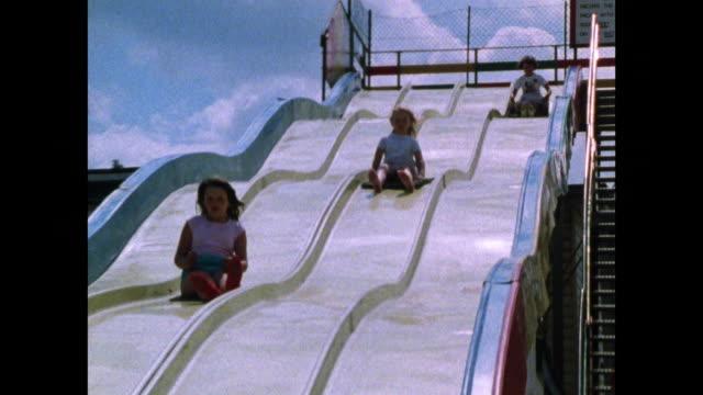 vidéos et rushes de children enjoying seaside amusement rides; 1986 - vacances