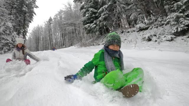 children enjoying sledding in winter forest. - imgorthand stock videos & royalty-free footage