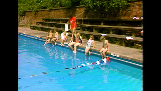 children enter outdoor pool at start of swimming lesson; 1984 - swimming costume stock videos & royalty-free footage