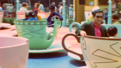 vidéos et rushes de children enter teacups / teacups spinning / mad tea party at disneyland theme park on may 10, 1973 in anaheim, california - parc d'attractions