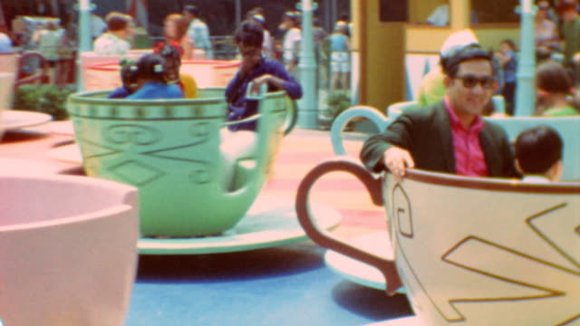vídeos de stock e filmes b-roll de children enter teacups / teacups spinning / mad tea party at disneyland theme park on may 10 1973 in anaheim california - chávena de chá