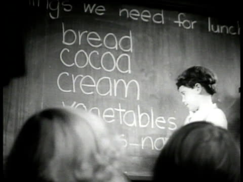 stockvideo's en b-roll-footage met children entering school building. int vs first graders writing foods on blackboard. int children in grocery store, grocer passing out foods. girl... - 1936