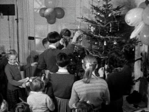 children excitedly decorate a christmas tree. 1962. - julglitter bildbanksvideor och videomaterial från bakom kulisserna