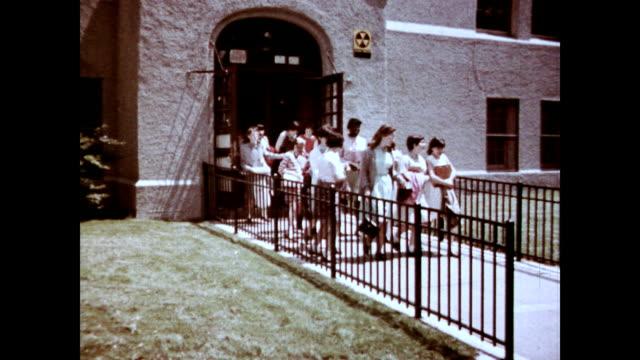 / children exiting a school building / children walking home from school children leaving school on january 01 1966 - 小学校点の映像素材/bロール