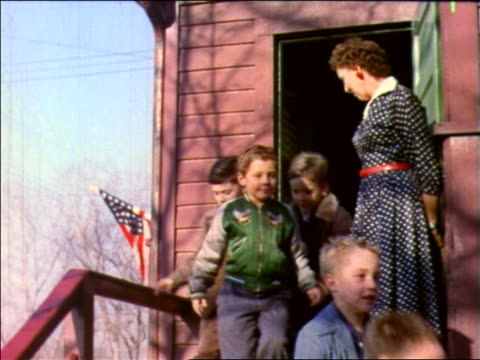 1957 children exiting schoolhouse with teacher holding door open / new jersey / industrial - 1957 stock-videos und b-roll-filmmaterial