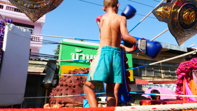 children fight muay thai omn a float during a parade at the ban bung fai rocket festival in yasothon thailand - muay thai stock videos and b-roll footage