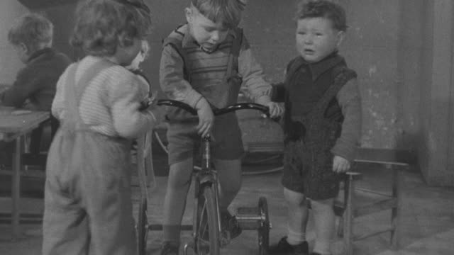 1947 ws children fighting over tricycle in nursery school / united kingdom - tricycle stock videos & royalty-free footage