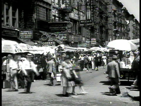 immigrants children gathered around enclosed turning merrygoround at street fair street vendors w/ umbrellas over stalls melting pot vs shop signs in... - judaism stock-videos und b-roll-filmmaterial