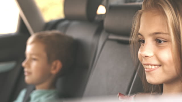 Children get in the car fastening seat belts
