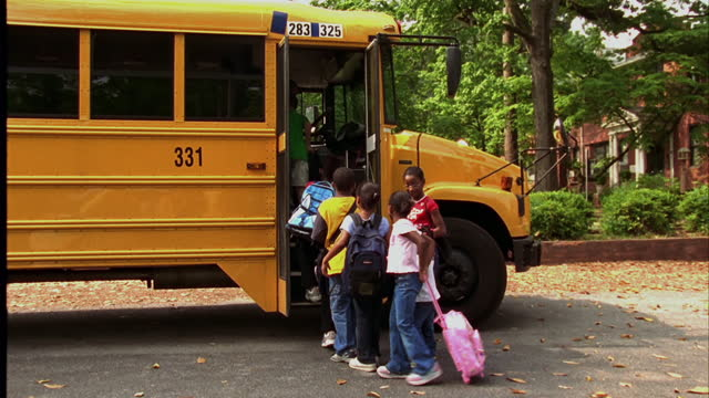 children get onto a school bus. - leaving stock videos & royalty-free footage