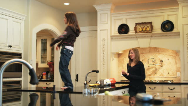 stockvideo's en b-roll-footage met children getting caught being mischievous - keuken huis